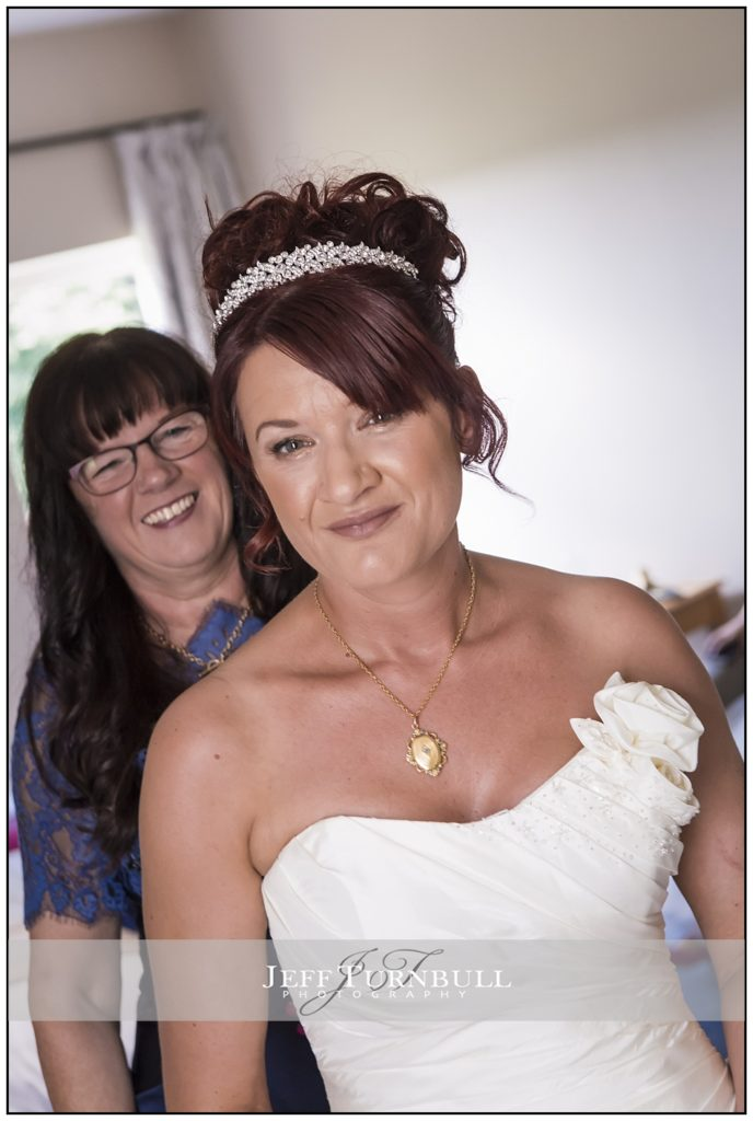 Mum doing up the brides dress