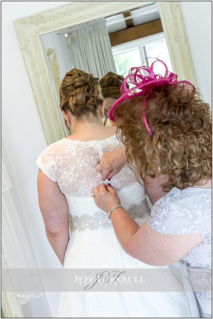 Bride Getting in her Wedding Dress